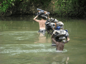 Teams protecting samples and kits as they cross a river in Central Africa