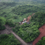Aerial view of RC drill rig and support vehicles drilling at one of the Abonko targets with spodumene bearing pegmatite boulders visible on the adjacent drill pad along the topographic high on the right-hand side of the photo