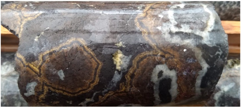 Detailed photo of zinc sulphide textures (see arrow above):iron rich sphalerite or marmatite (purple) with bands of later low iron sphalerite (brown and yellow) and quartz (white).The banding of the zinc sulphides highlights multiple stages of zinc mineralization at Ayawilca.